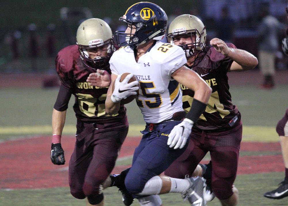 Unionville's Jack Adams fights for yards against Avon Grove, Friday. Jim Gill photo.