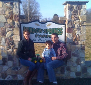 Jamie Hicks (from left) sits with his son, Graham, and wife Kate at the entrance to Meadow Springs Farm.