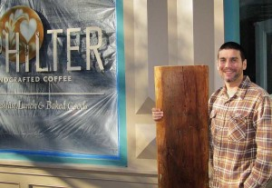Chris Thompson, proprietor of Philter, a new coffee shop in Kennett Square, cradles a large slab of sculptured pine that soon will become a bench seat in the front window of the new shop he plans to open in late November.